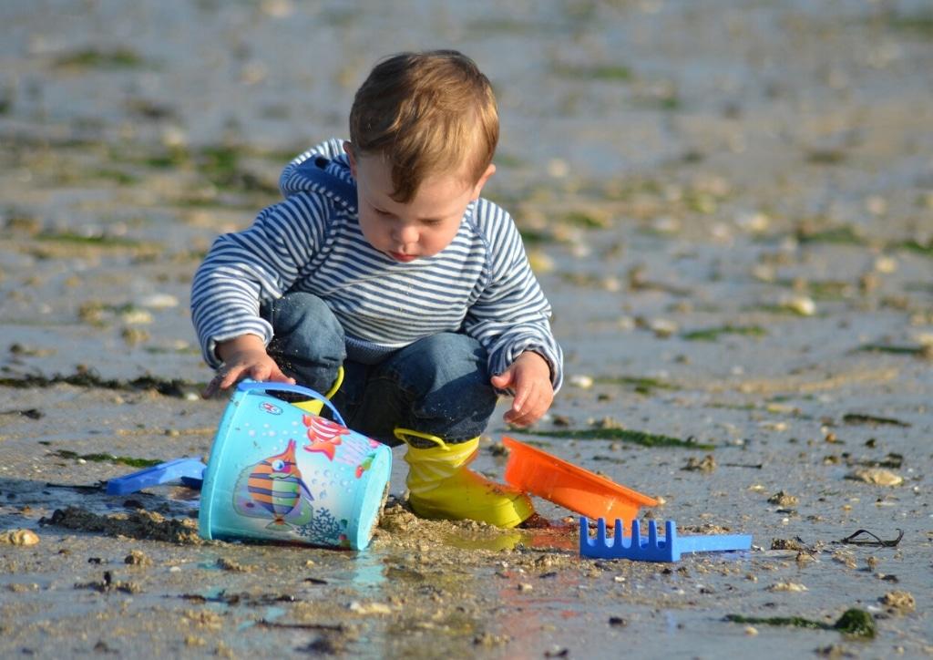 Enfant jouant seul à creuser et construire dans le sable sur la plage